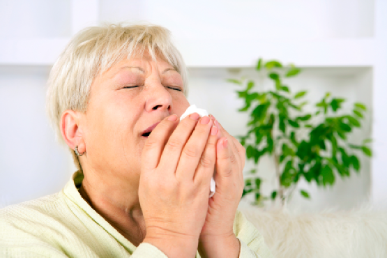 Senior woman sneezing
